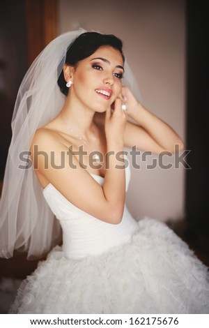 Beautiful young caucasian bride is getting ready at home. - stock photo