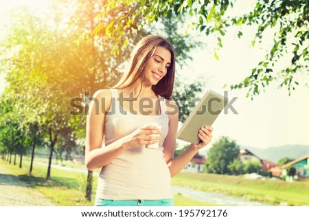 Beautiful young Caucasian brunette woman in park in summer with tablet computer and takeaway coffee. She is wearing beige tank top and green shorts. Back lit. Modern lifestyle concept. - stock photo