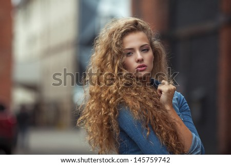 Beautiful young Caucasian girl with curly hair outdoors - stock photo