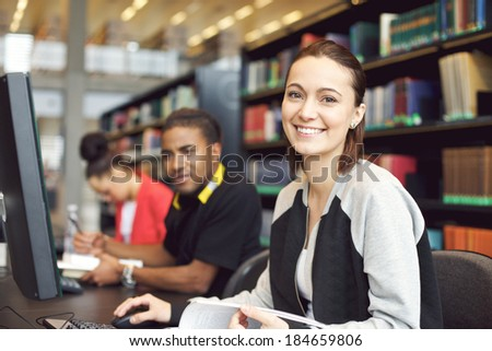 Beautiful young caucasian student sitting at table with computer looking at camera smiling. Young university students researching information on computer for their studies. - stock photo