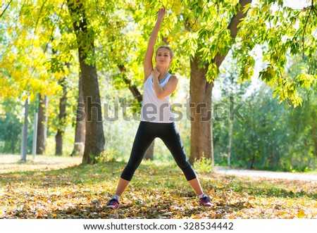 Beautiful young caucasian woman in fitness wear working out in a park - stock photo