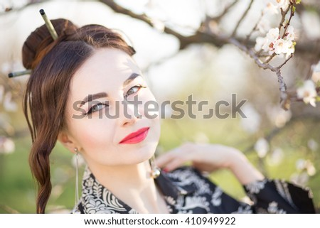 Beautiful young caucasian woman near blooming tree. Thoughtful girl with blossoming cherry-tree - stock photo