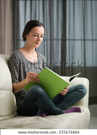 beautiful young caucasian woman reading book on couch at home - stock photo