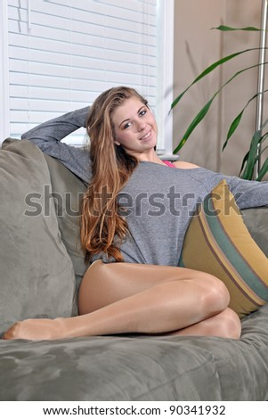 Beautiful young Caucasian woman relaxing on couch in oversized grey t-shirt - stock photo