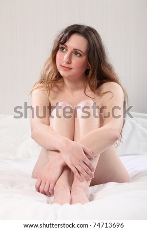 Beautiful young caucasian woman, sitting naked on her bed with knees raised to an implied nude pose. - stock photo