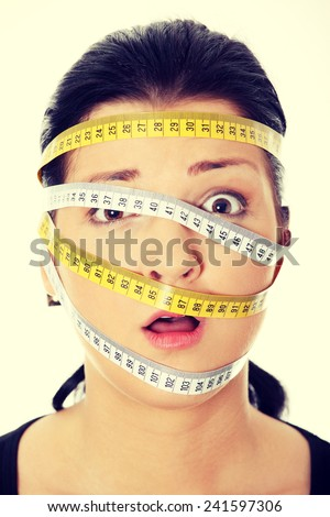 Beautiful young caucasian woman with measuring tape around her head. Diet concept - stock photo