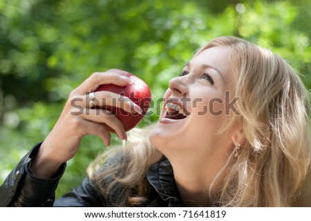 Beautiful young cheerful woman has turned in profile and bites red big apple, against green garden. - stock photo