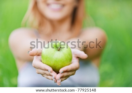 Beautiful young cheerful woman with green big apple, against green summer garden. - stock photo