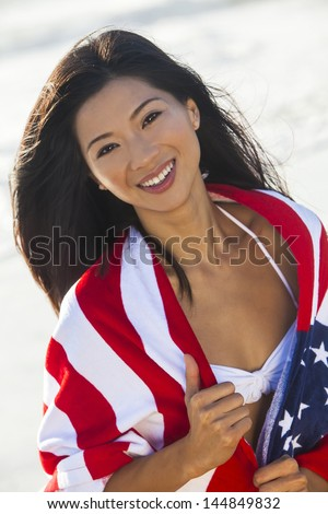 Beautiful young Chinese Asian woman laughing wearing bikini and wrapped in American flag towel on a sunny beach - stock photo