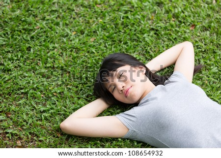 Beautiful young Chinese lady sleeping on grass with room for copyspace.
