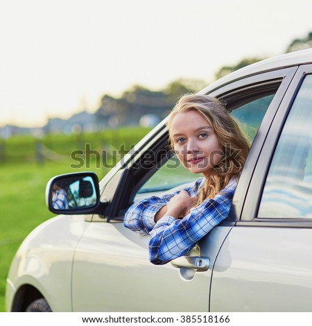 Beautiful young confident woman driving a car