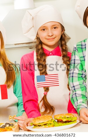 Beautiful young cook with hamburgers on the plate