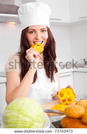 beautiful young cook with  vegetables in the kitchen - stock photo