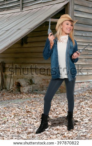 Beautiful young country girl woman wearing a stylish cowboy hat and revolvers - stock photo