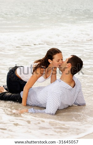 beautiful young couple  at the beach, about to kiss as the tide comes up and covers them with water, getting washed away. - stock photo