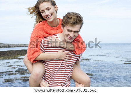 Beautiful young couple at the beach. They are smiling and the young woman is having a piggyback from her boyfriend.  - stock photo