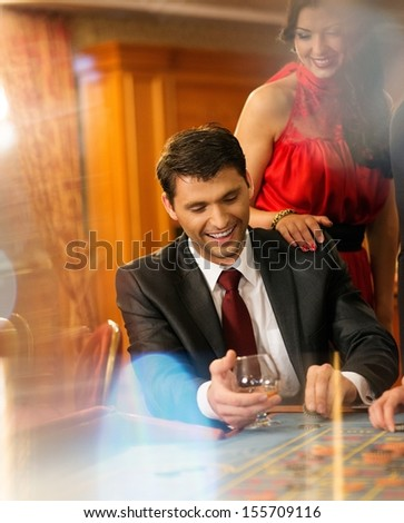 Beautiful young couple behind roulette table in a casino - stock photo