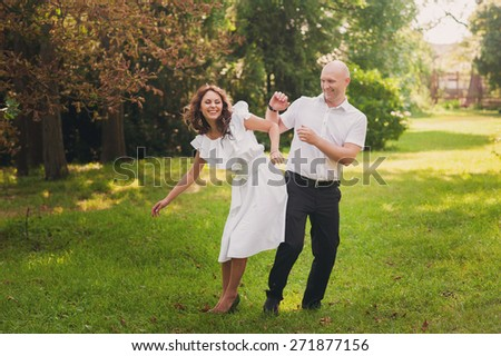 Beautiful young couple dancing and having fun around on the green grass, lifestyle, love, laugh, smile
