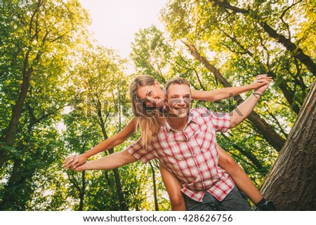 Beautiful young couple enjoying a piggyback in the forest. - stock photo