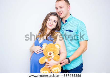 Beautiful young couple expecting baby. Portrait of young couple expecting baby Husband hugs his pregnant wife  - stock photo