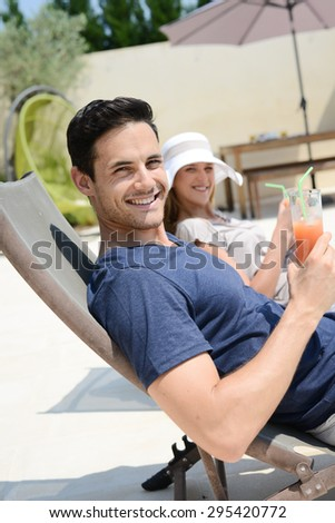 beautiful young couple having drink in deck chairs by the pool in holiday resort