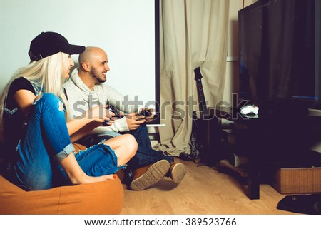 Beautiful young couple having fun and playing computer games. concept of leisure entertainment and fun - stock photo