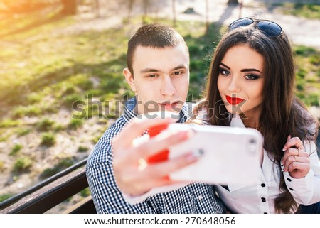 beautiful young couple having fun on a bench in the park - stock photo