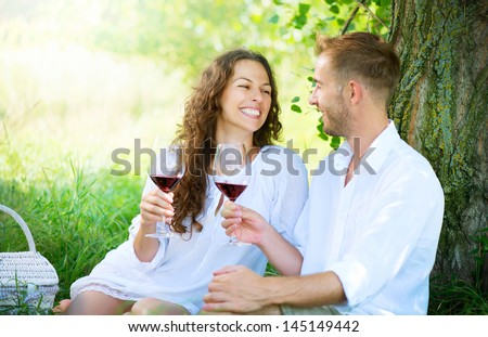 Beautiful Young Couple Having Picnic in Countryside. Happy Family Outdoor. Smiling Man and Woman relaxing and drinking Wine in Park. Relationships - stock photo