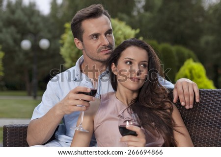 Beautiful young couple having red wine in park - stock photo