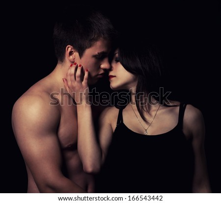Beautiful young couple hugging and kissing isolated on black background. - stock photo