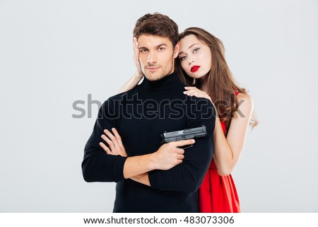 Beautiful young couple hugging and posing with gun