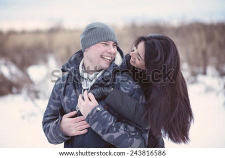 Beautiful young couple hugging and smiling in winter park. Happy family.