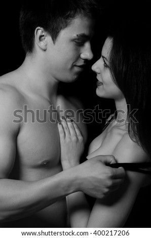 Beautiful young couple hugging and touching isolated on black background.