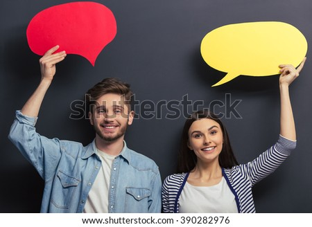 Beautiful young couple in casual clothes is holding colorful speech bubbles, looking at camera and smiling, standing against blackboard - stock photo