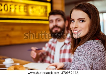 Beautiful young couple in casual clothes working and communicating while sitting in a cafe