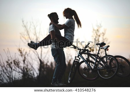 Beautiful young couple in love at sunset, man holds the girl on hands, there are two bikes. The concept of desire, passion and love