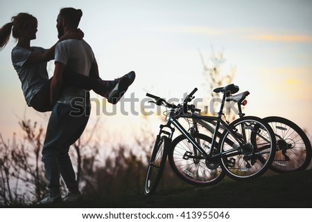 Beautiful young couple in love at sunset, man holds the girl on hands, there are two bikes. The concept of desire, passion and love - stock photo