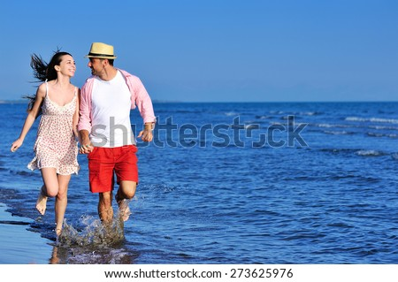 Beautiful young couple in love enjoying walking and running on the beach - stock photo