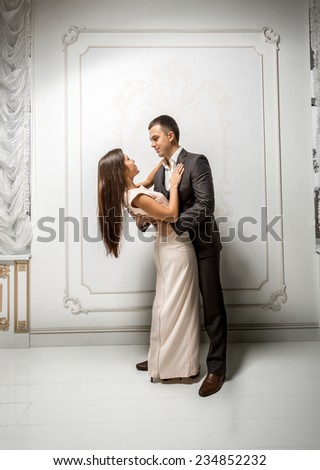Beautiful young couple in love hugging in classic interior - stock photo
