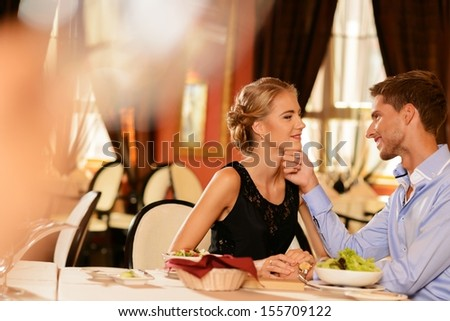 Beautiful young couple in love in restaurant - stock photo