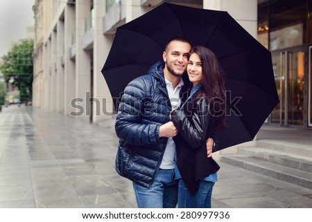 Beautiful young couple in love on a date outdoors on modern urban background. Smiling and hugging. Bearded handsome man and brunette pretty woman in casual dress with umbrella. Rainy weather. - stock photo