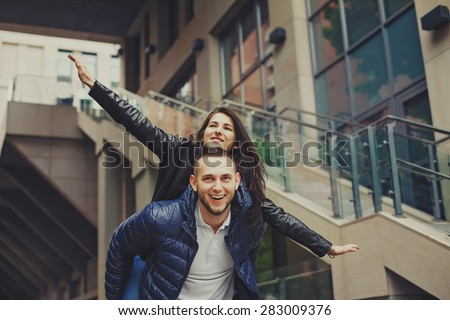 Beautiful young couple in love on a date outdoors on modern urban background. Smiling and hugging. Bearded handsome rustic man and brunette pretty woman in casual dress. - stock photo
