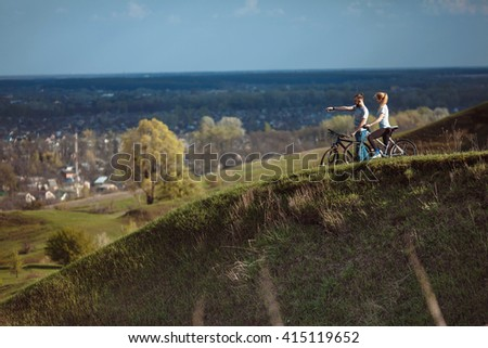 Beautiful young couple in love on bicycles on the walk come from the mountains - stock photo