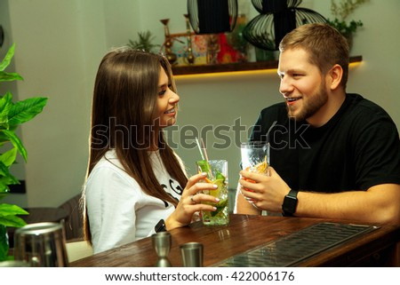 beautiful young couple in love sitting at the bar drinking cocktails and flirting - stock photo