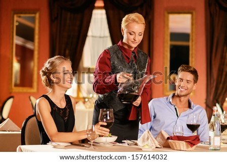 Beautiful young couple in restaurant and waitress pouring wine