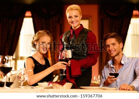 Beautiful young couple in restaurant and waitress with bottle of red wine  - stock photo