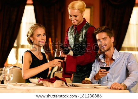 Beautiful young couple in restaurant and waitress with bottle of wine