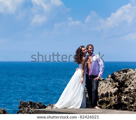 Beautiful young couple in the background of the ocean and rocks - stock photo