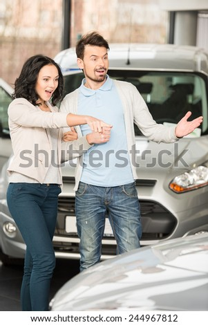 Beautiful young couple in the showroom, choosing a car. - stock photo