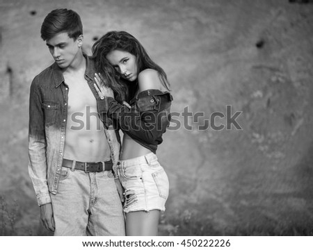 Beautiful young couple in trendy jeans clothes posing outdoor. Casual style. black and white photo. - stock photo